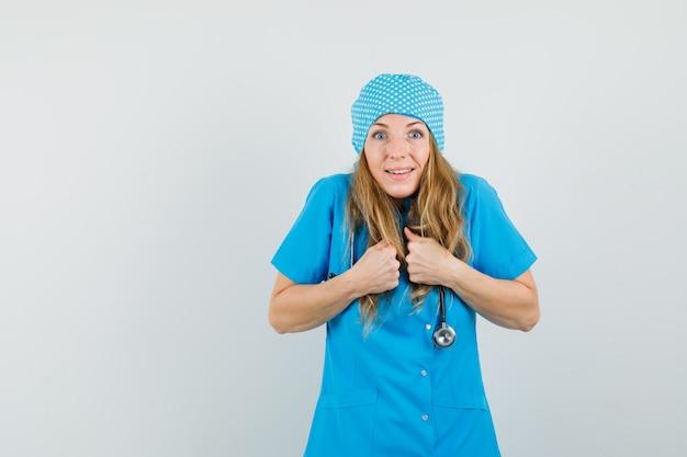 Femme médecin gardant les poings sur la poitrine en uniforme bleu et à l'air heureux.
