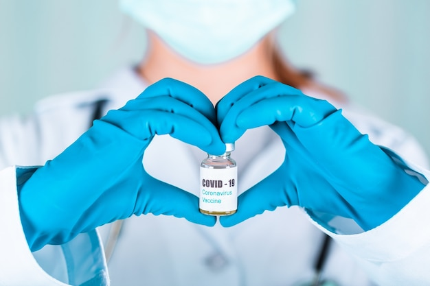 Femme médecin ou infirmière en uniforme et gants portant un masque de protection en laboratoire tenant dans une forme de flacon de vaccin pour flacon de médecine cardiaque avec étiquette de vaccin covid-19 contre le coronovirus