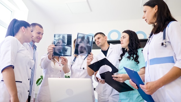 Femme médecin et jeunes internes en médecine en vêtements médicaux étudiant ensemble les résultats de la radiographie pulmonaire...