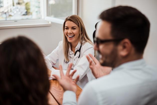 Femme médecin joyeuse, discutant avec le jeune couple au bureau.