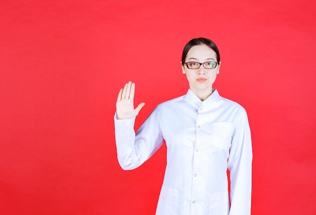 Femme médecin à lunettes debout sur fond rouge et arrêtant quelque chose avec des gestes de la main.