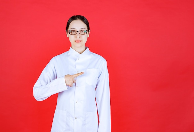 Femme médecin à lunettes debout sur fond rouge et montrant le côté droit.