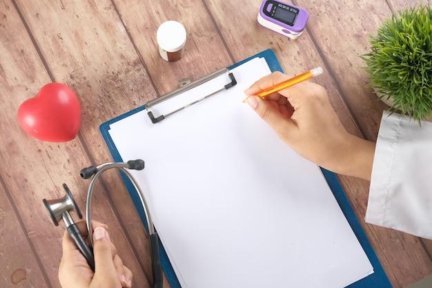 Femme médecin main écrit la prescription sur la vue de dessus de bureau