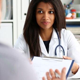 Femme médecin main tenir stylo argenté et montrant