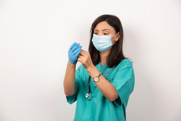 Femme médecin avec masque médical portant des gants sur fond blanc.