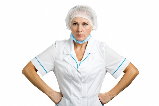 Femme médecin mature sérieuse. portrait de femme médecin en colère isolé sur blanc. femme médecin mature sévère gardant les mains sur les hanches et donnant des instructions.