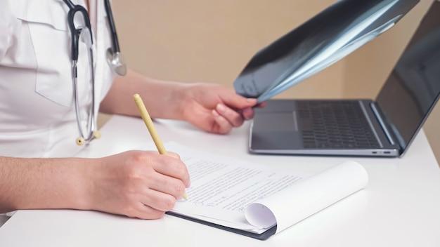 Une femme médecin méconnaissable en robe blanche travaille avec des images radiographiques et des papiers prenant des notes sur le presse-papiers, assise à table avec un ordinateur portable moderne en gros plan de bureau