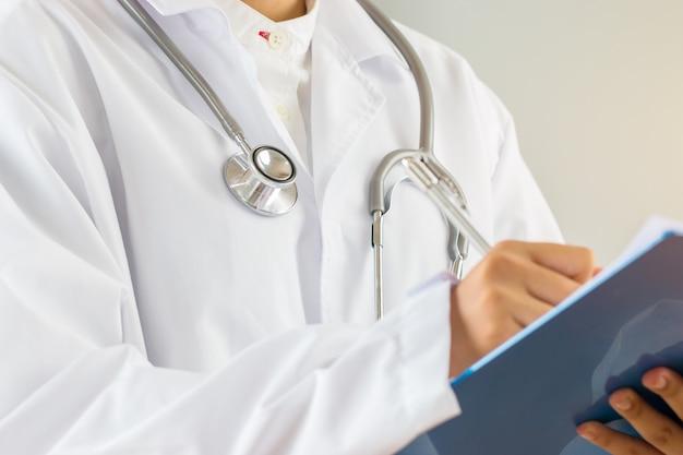 Femme médecin médecin écrit le presse-papiers de prescription avec du papier d'enregistrement