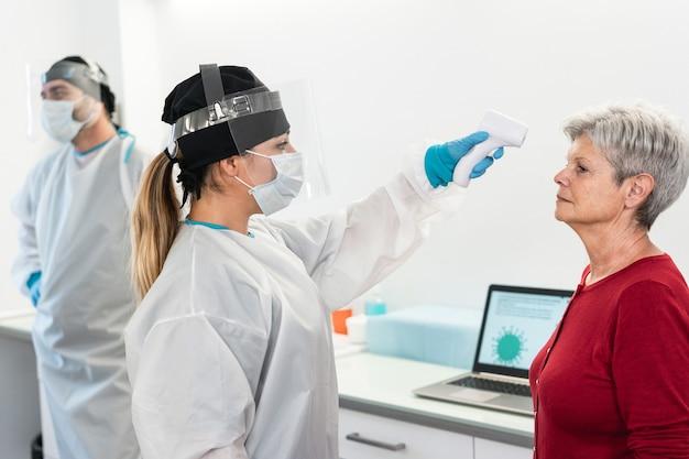 Femme médecin mesurant la température d'un patient senior pour une maladie à coronavirus