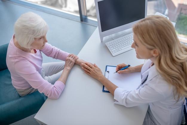 Femme médecin mettant sa main sur la main du patient montrant son soutien