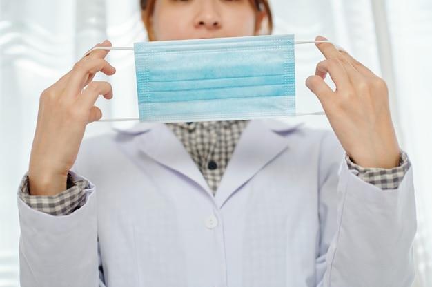 Femme médecin montrant comment mettre un masque médical