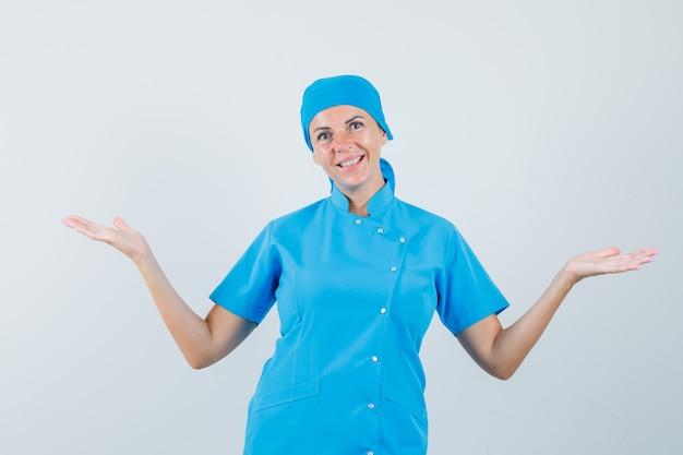 Femme médecin montrant ou comparant quelque chose en uniforme bleu et à la recherche de bonne humeur. vue de face.