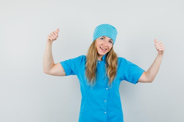 Femme médecin montrant deux pouces vers le haut en uniforme bleu et l'air heureux.