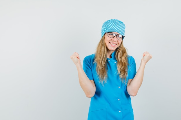 Femme médecin montrant le geste gagnant en uniforme bleu et à la béatitude.