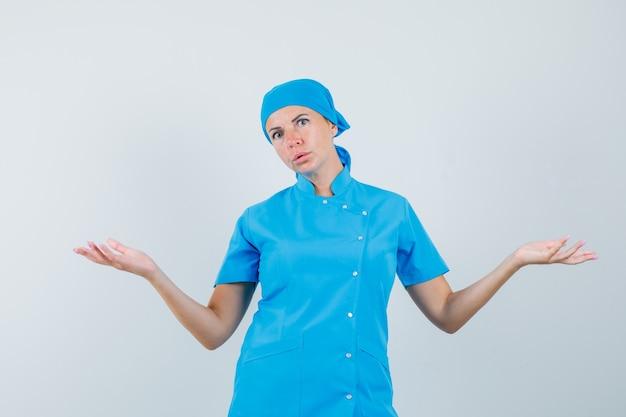 Femme médecin montrant un geste impuissant en uniforme bleu et à la confusion. vue de face.