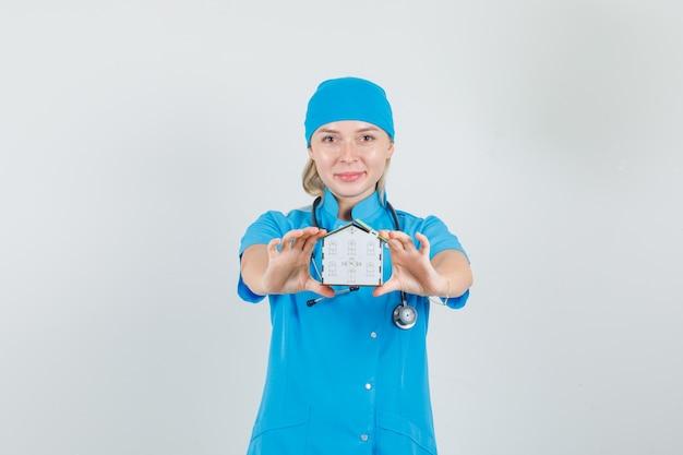 Femme médecin montrant le modèle de la maison et souriant en uniforme bleu