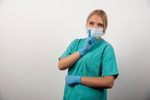 Femme médecin montrant le pouce vers le haut et portant un masque médical.