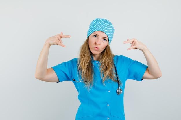 Femme médecin montrant signe de roche en uniforme bleu et à la confiance
