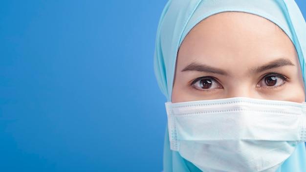 Une femme médecin musulman avec hijab portant un masque chirurgical sur bleu