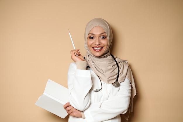 Femme médecin musulmane arabe tenant un journal et pointant avec un crayon blanc sur un beige