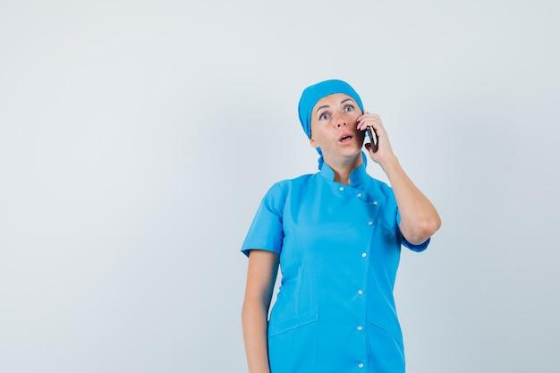 Femme médecin parlant au téléphone mobile en uniforme bleu et à la surprise. vue de face.