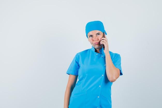 Femme médecin parlant au téléphone mobile en uniforme bleu et à la vue de face, hésitante.