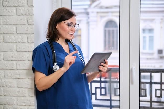 Femme médecin parlant en ligne avec un patient à l'aide d'une tablette numérique, appel vidéo, technologie, médecin près de la fenêtre du bureau de la clinique