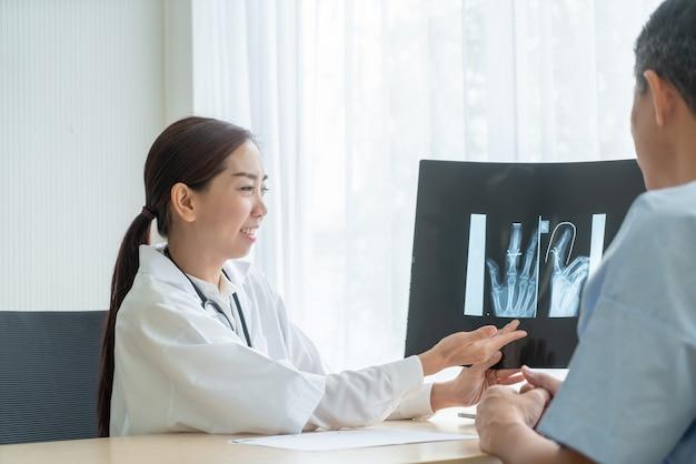 Femme médecin et patient asiatique discutant de quelque chose tout en étant assis à la table