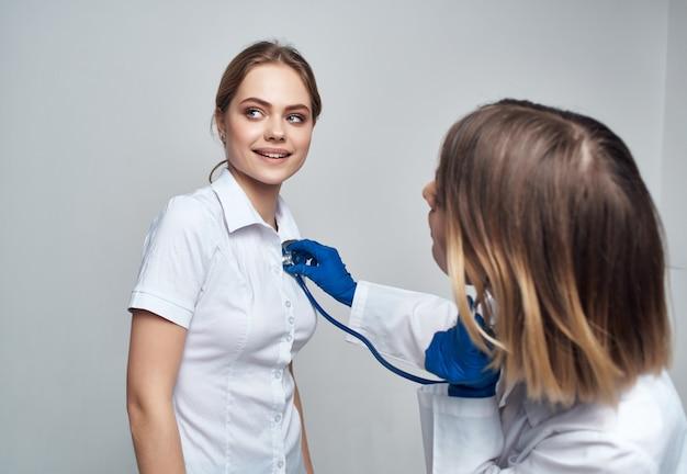 Femme médecin patient examen soins de santé fond clair