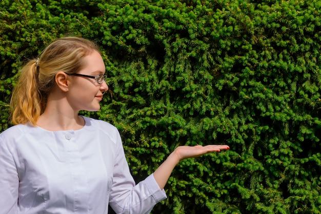 Femme médecin avec paume vers le haut. scientifique en blouse blanche et lunettes sur vert naturel avec espace de copie. image pour la publicité des développements scientifiques dans l'industrie alimentaire et médicale.