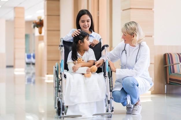 Femme médecin pédiatre et enfant patient en fauteuil roulant avec sa mère dans le centre médical de santé