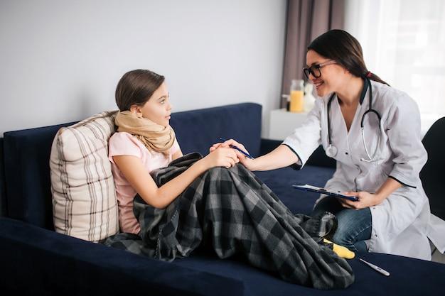 Une femme médecin perturbatrice est assise à côté d'une fille malade. elle tient sa main et regarde l'enfant. docteur sourire. petite fille regarde professionnel. ils restent dans une pièce.