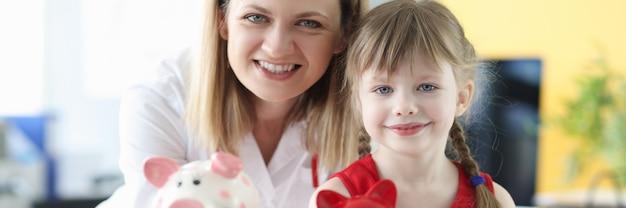 Femme médecin et petite fille tenant des tirelires. concept d'assurance maladie pour les enfants