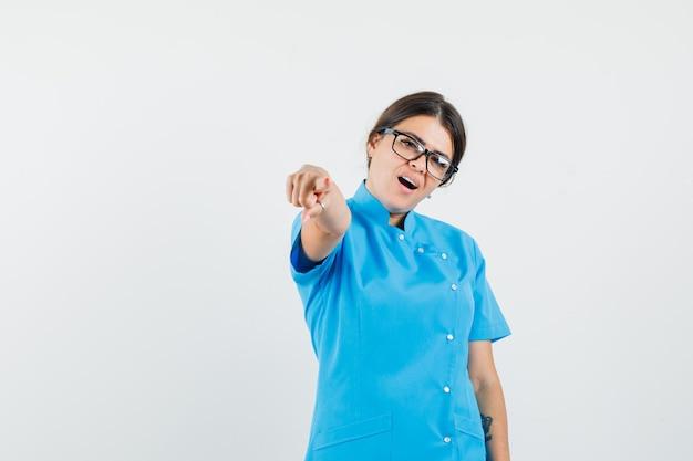 Femme médecin pointant sur la caméra en uniforme bleu et à la confiance