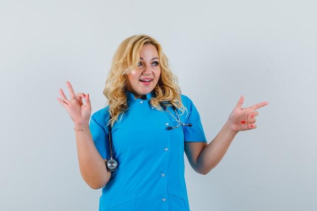 Femme médecin pointant de côté tout en montrant un geste ok en uniforme bleu et à la recherche de plaisir.
