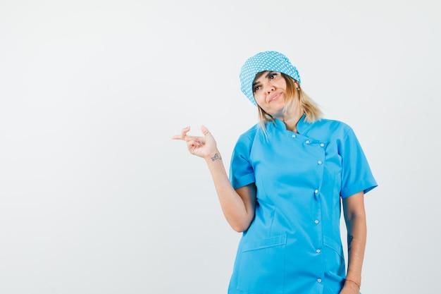 Femme médecin pointant sur le côté en uniforme bleu et à la recherche de rêve