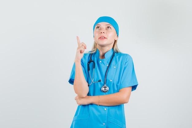 Femme médecin pointant le doigt en uniforme bleu et à la recherche d'espoir