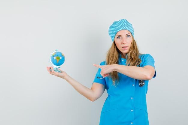 Femme médecin pointant sur globe en uniforme bleu