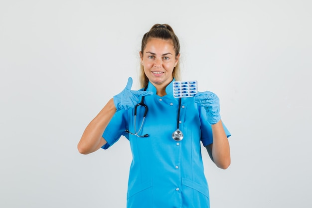 Femme médecin pointant sur pack de capsules en uniforme bleu