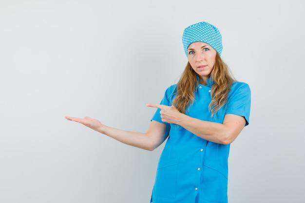Femme médecin pointant sur la paume écartée en uniforme bleu
