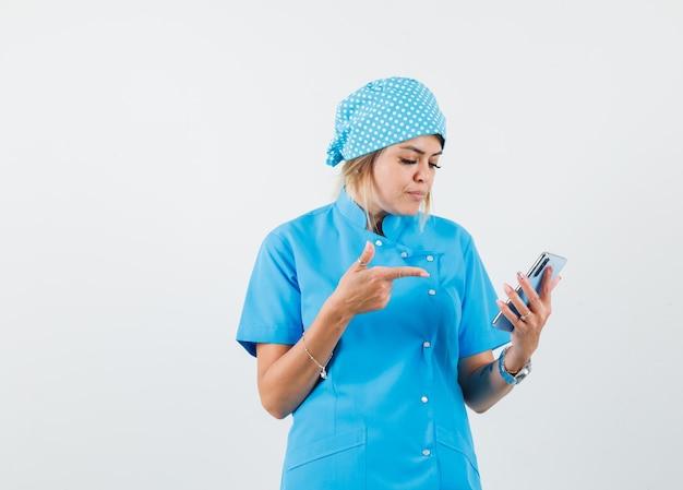 Femme médecin pointant sur téléphone mobile en uniforme bleu et à l'accent