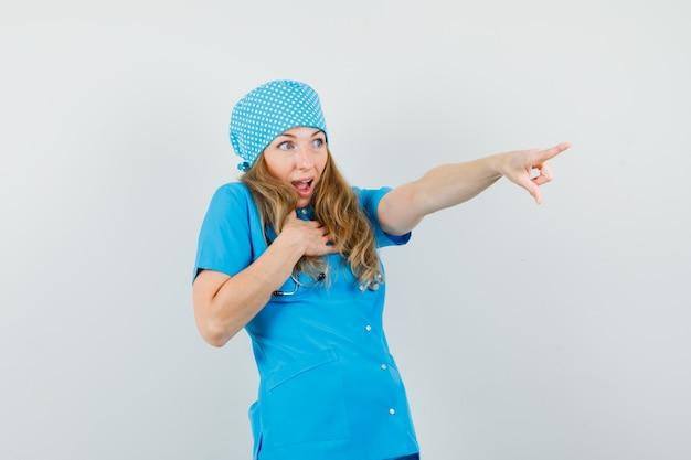 Femme médecin pointant vers l'extérieur en uniforme bleu et à la surprise.
