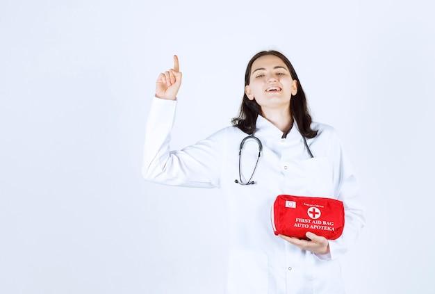Femme médecin pointant vers le haut tout en tenant son sac médical et souriant devant le mur rouge