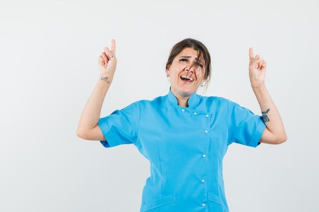 Femme médecin pointant vers le haut en uniforme bleu et à heureux
