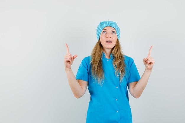 Femme médecin pointant vers le haut en uniforme bleu et à la recherche d'espoir