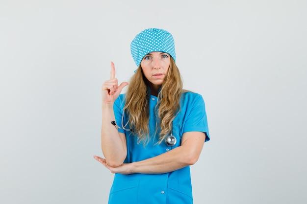 Femme médecin pointant vers le haut en uniforme bleu et à la recherche sensible.