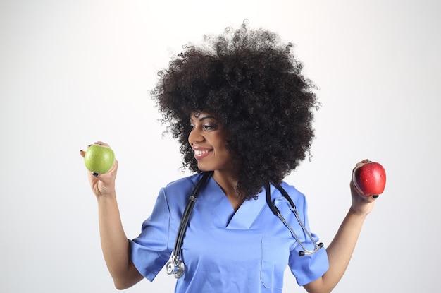 Femme médecin avec une pomme à la main, fond blanc femme afro, concept de vie saine, santé
