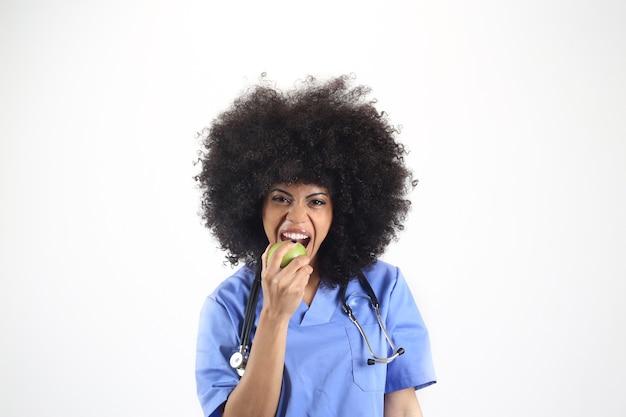 Femme médecin avec une pomme à la main, fond blanc femme afro