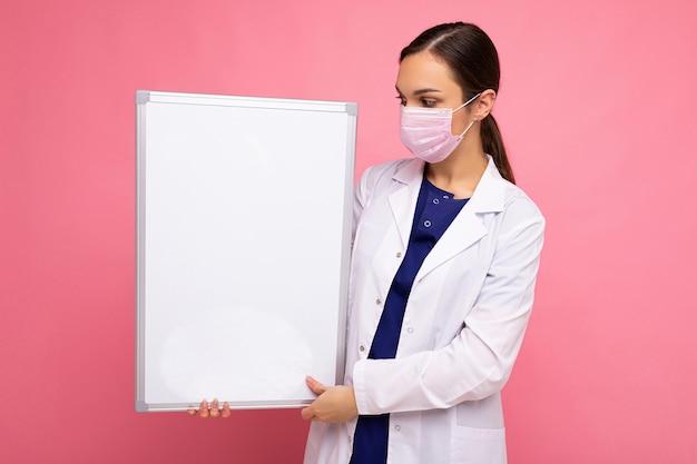 Femme médecin portant une blouse blanche et un masque tenant un tableau blanc avec espace de copie pour le texte isolé sur fond. concept de coronavirus.