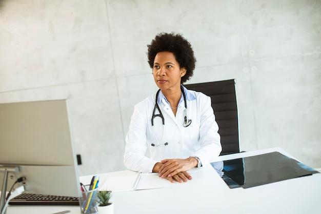 Femme médecin portant une blouse blanche avec stéthoscope assis derrière un bureau au bureau